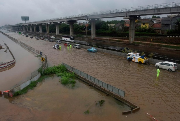 Những cơn mưa lớn khiến đường phố ở Bekasi hóa thành sông hồ - Ảnh: Reuters.