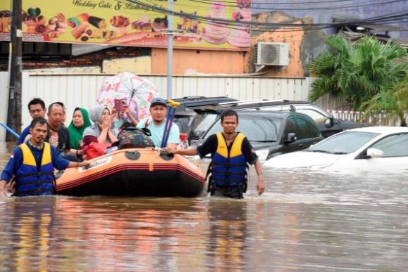 Đội cứu hộ dùng thuyền hơi đưa người dân ở Bekasi, gần Jakarta, đến nơi an toàn hôm 1/1 - Ảnh: Reuters.