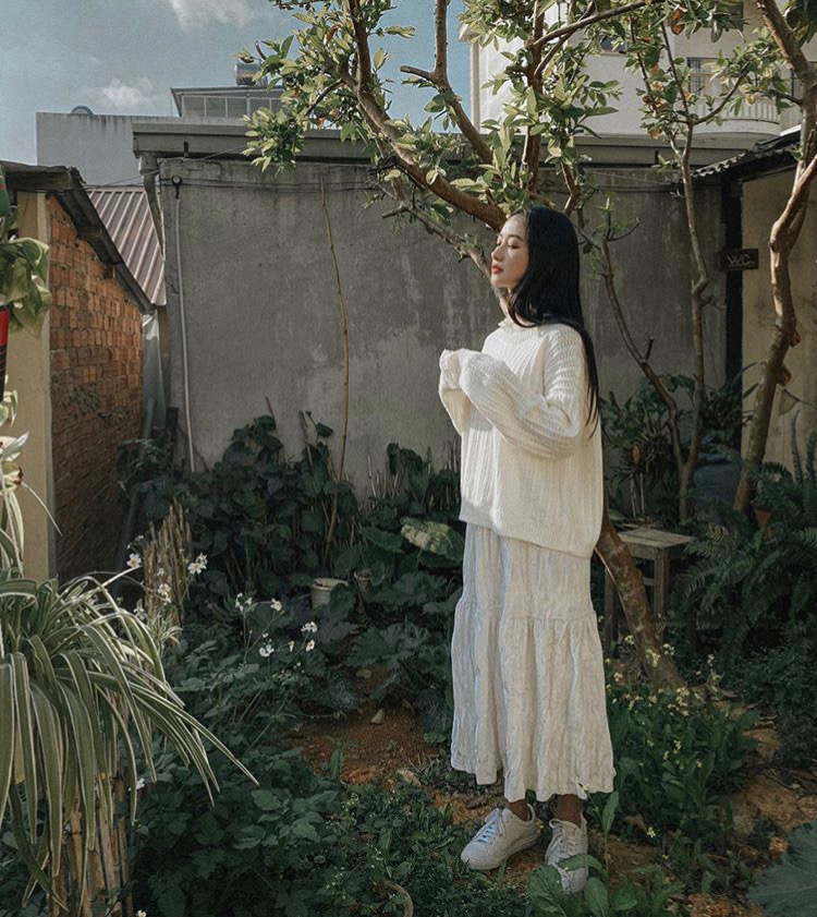 Jun Vũ tận hưởng không khí mát lạnh của Đà Lạt dịp năm mới với set đồ áo len mix cùng chân váy dài đi kèm sneaker năng động.