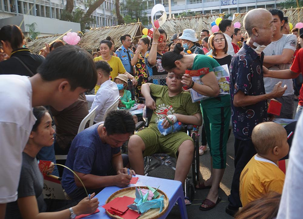 Các bé vận động khó khăn do di chứng của căn bệnh quái ác ngồi xe lăn đến xếp hàng, nhờ các anh chị tình nguyện viên viết và xếp hạc giấy.