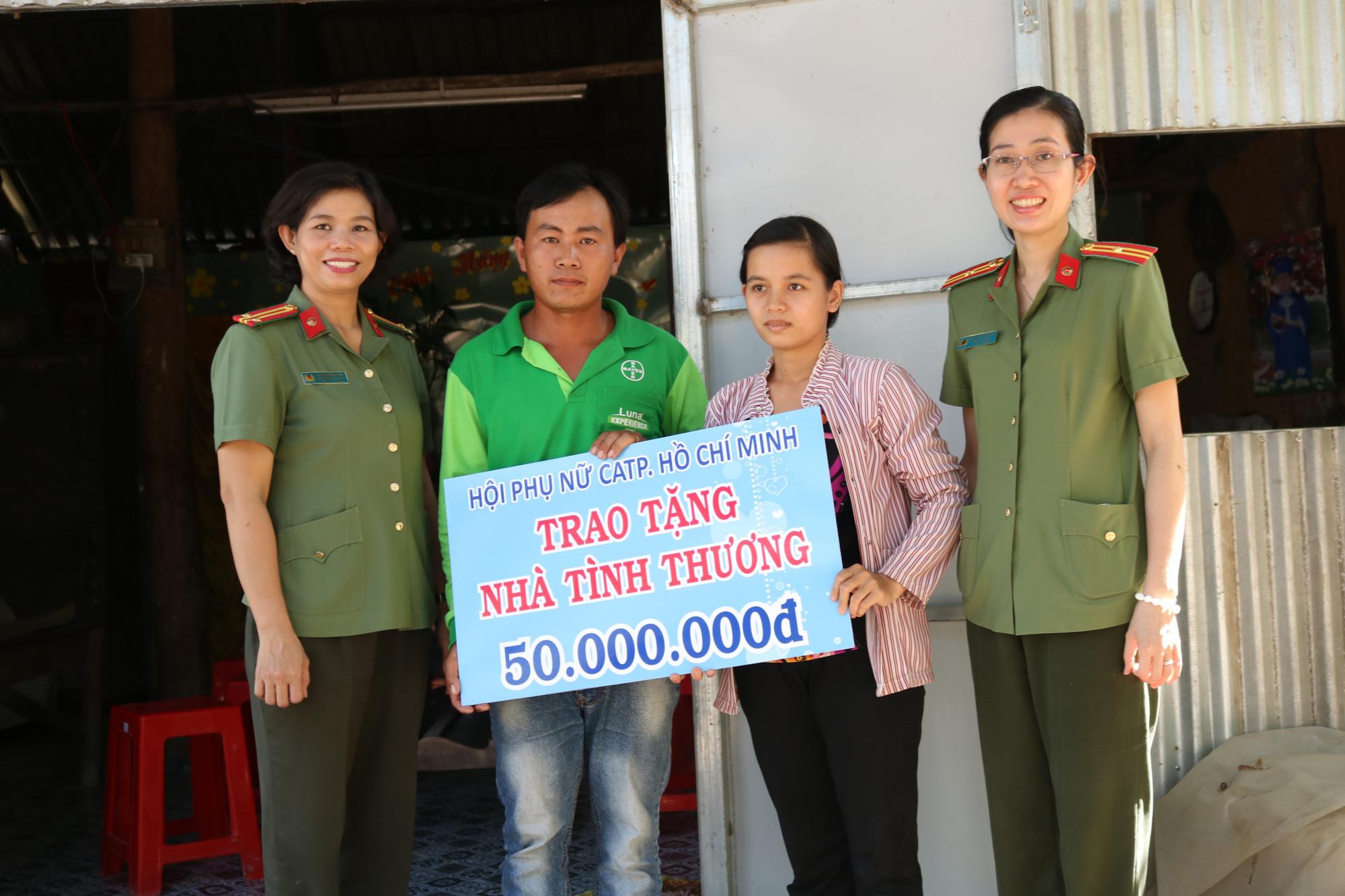 Vợ chồng anh Huy nhận bảng tượng trưng kinh phí do Hội Phụ nữ Công an TP.HCM hỗ trợ để xây nhà.