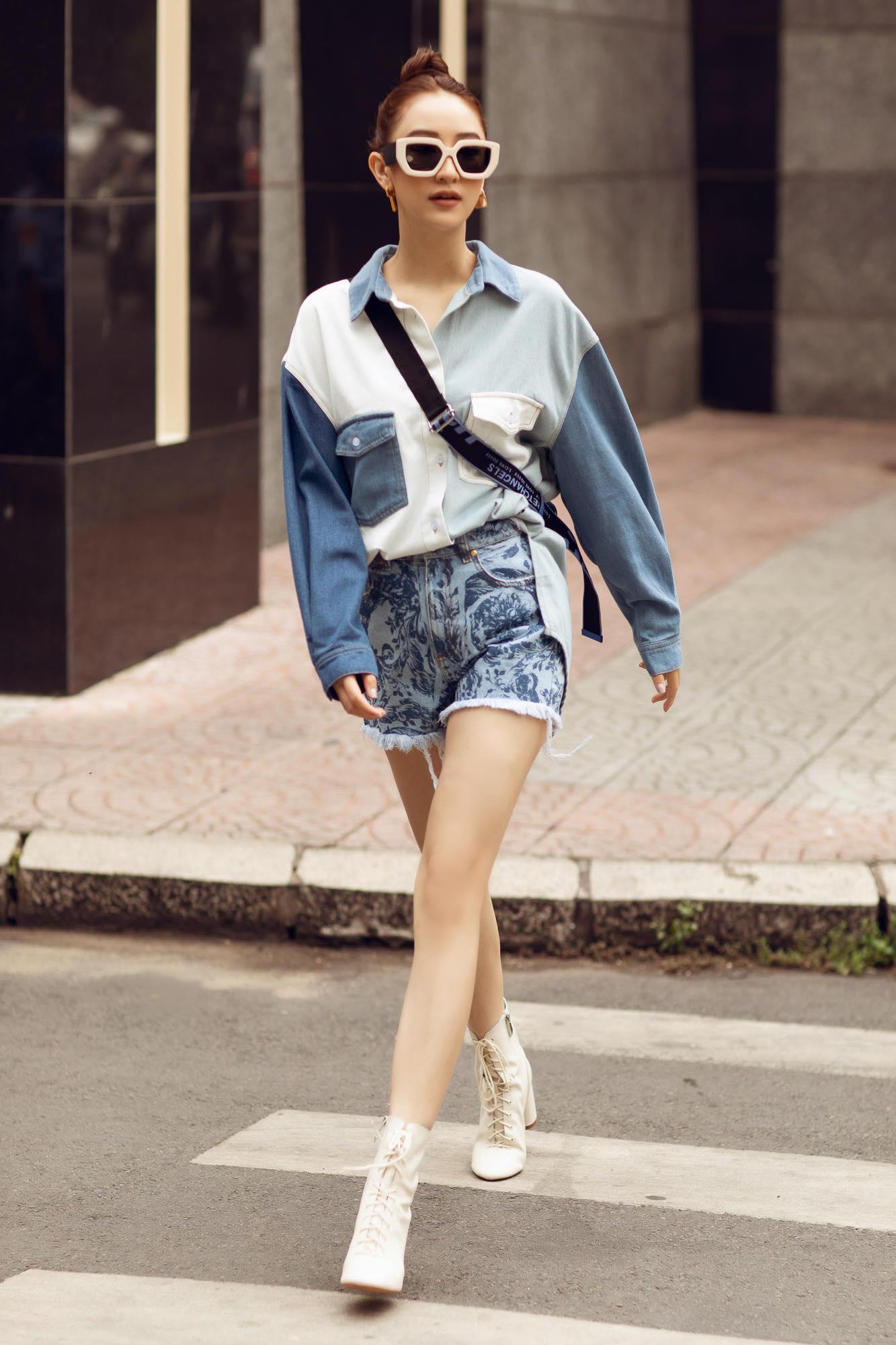 Diện áo và chân váy Versace Jeans kết hợp túi Balenciaga, mắt kính Dior tạo nên tổng thể cá tính, khoe trọn lợi thế hình thể chuẩn cùng đôi chân dài miên man của người đẹp. Ngoài ra, cô nàng còn khéo léo mix cùng boot trắng cổ thấp giày Saint Laurent tăng tính thời thượng cho set đồ.