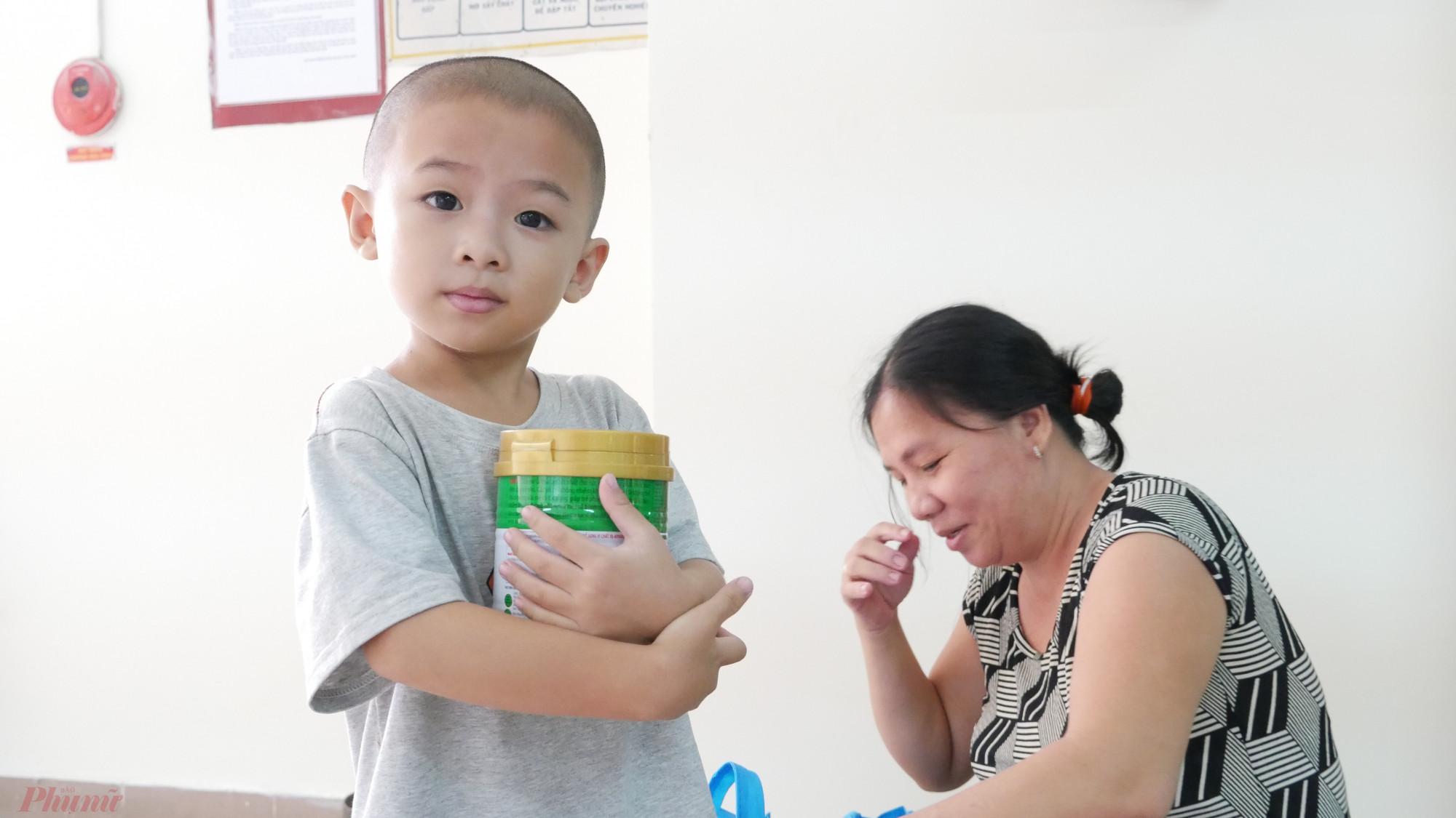 Niềm vui của đứa trẻ theo bà đi nhận quà tết.