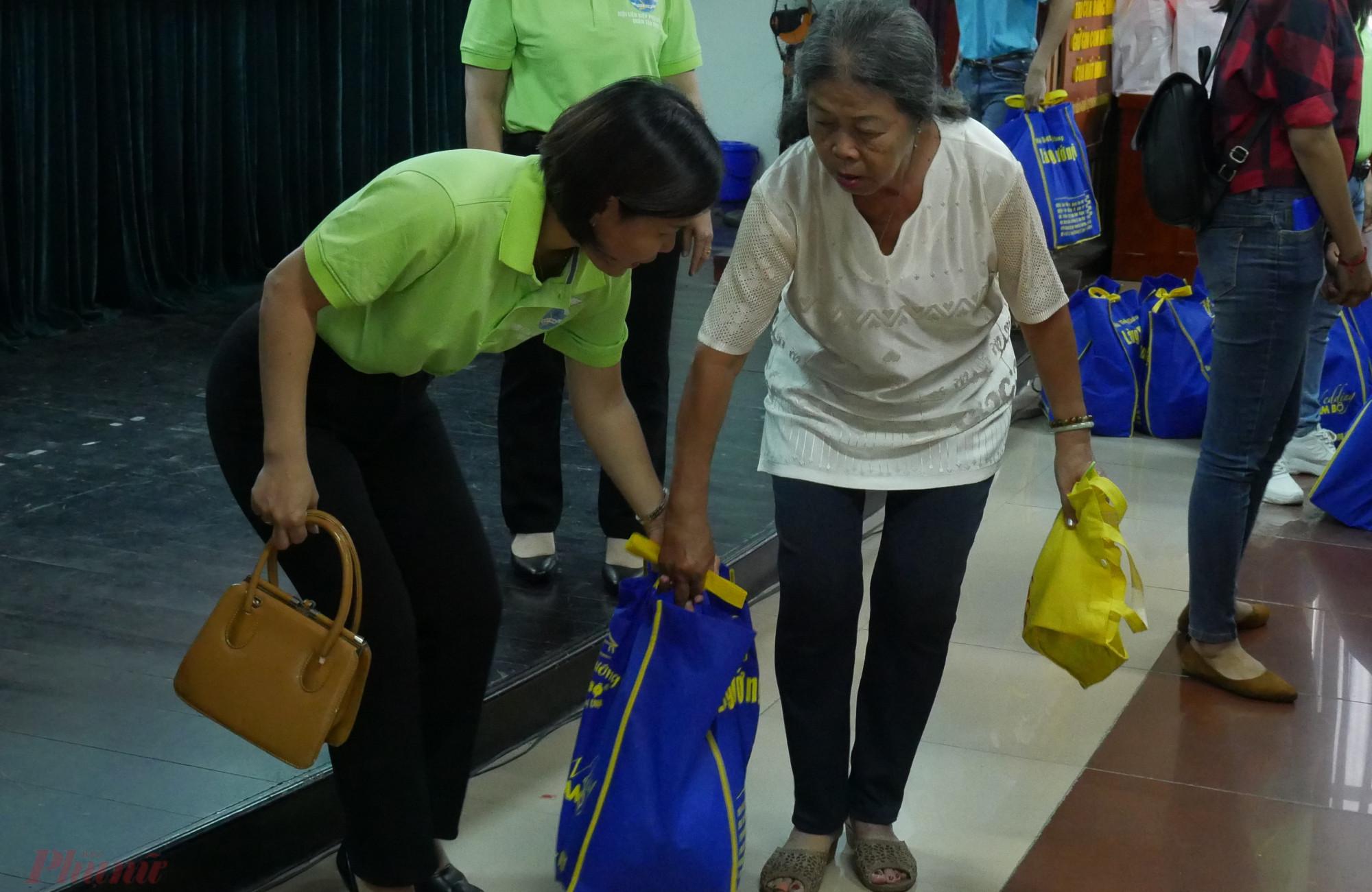 Chị Đặng Thị Hồng Vân - Chủ tịch Hội LHPN quận Tân Phú giúp các chị mang những phần quà tết ra về.