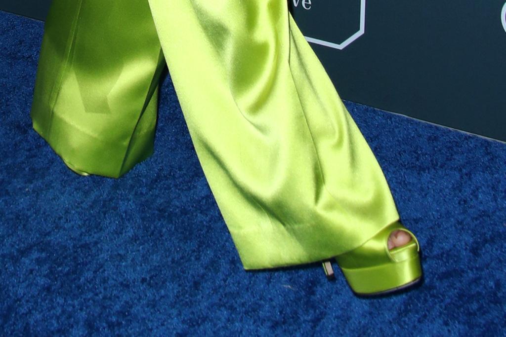 Nữ diễn viên kết hợp trang phục cùng clutch, hoa tai ánh bạc cùng giày cao đồng màu xanh. Bộ trang phục giúp Kristen Bell trông cao hơn nhiều so với chiều cao thực tế 1m55.