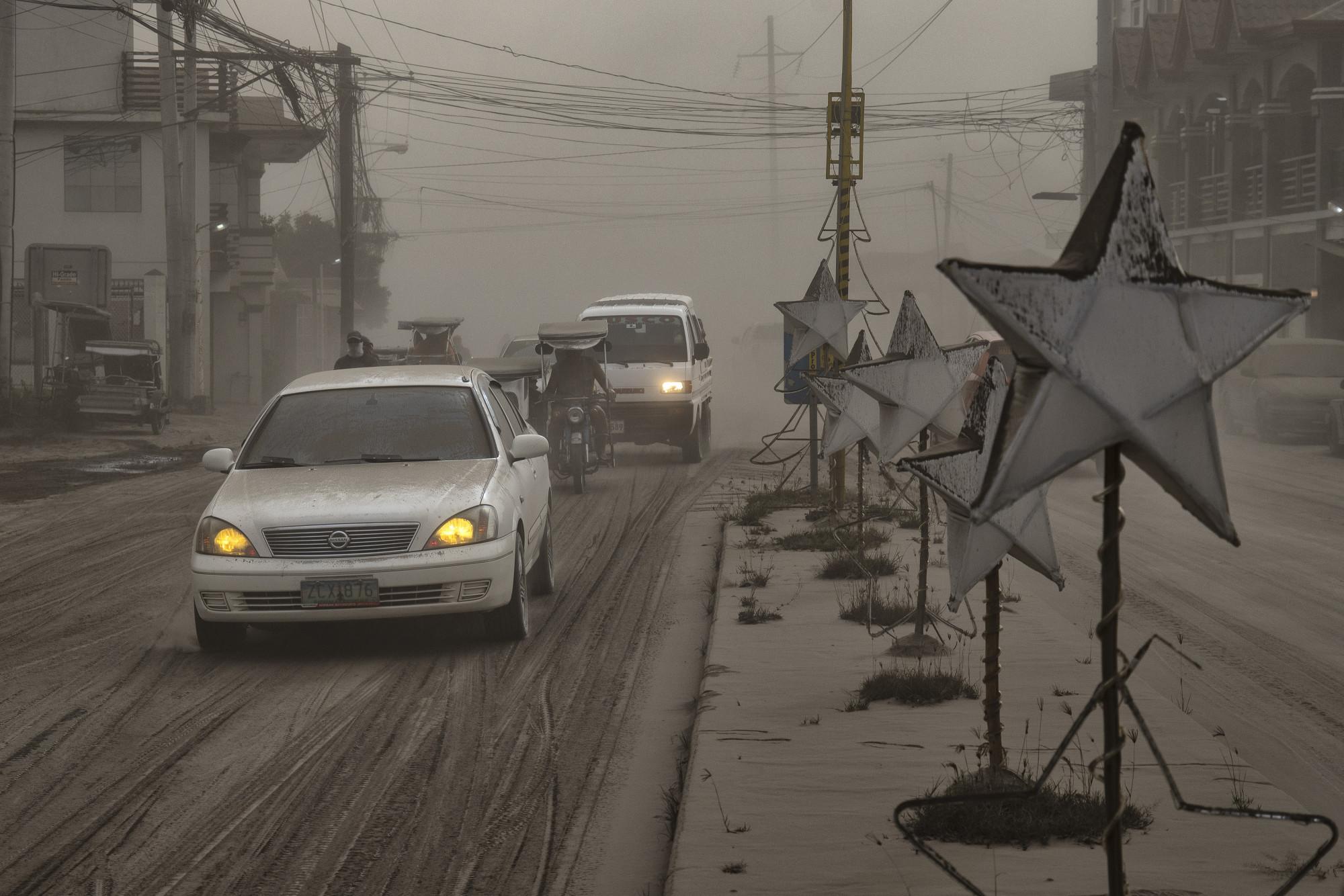 Những chiếc xe băng qua một con đường phủ đầy tro núi lửa từ vụ phun trào của núi lửa Taal vào ngày 13 tháng 1 năm 2020, ở Lemery, tỉnh Batangas, Philippines. Hình của Ezra Acayan (nguồn: Getty Images)