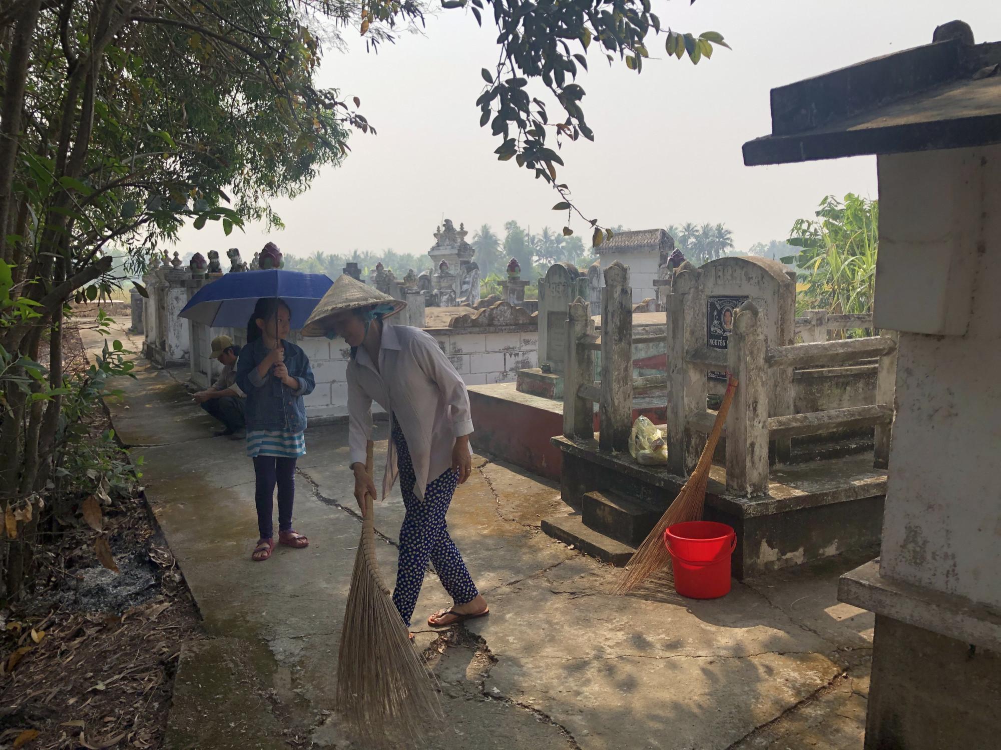 Trước Tết dù bận tới đâu người dân Nam bộ cũng thu xếp ra quét dọn, viếng thăm phần mộ của ông bà. Ảnh: Thanh Huyền.