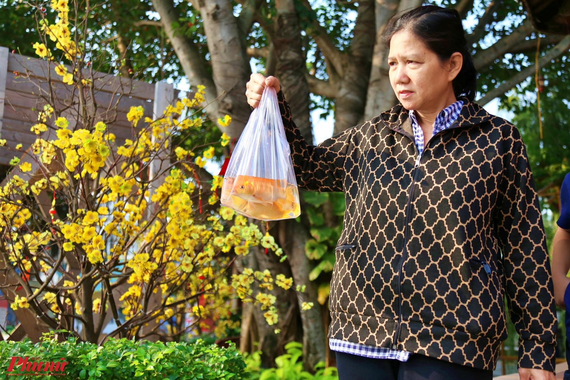 Sáng sớm ngày 17/1, tức ngày 23 tháng Chạp, nhiều người dân Sài Gòn đã làm lễ cúng tiễn ông Công ông Táo về trời.  Trong ảnh chị  Liên ở quận Bình Thạnh tranh thủ thả cá chép trên sông Sài Gòn sau khi cúng ông Táo