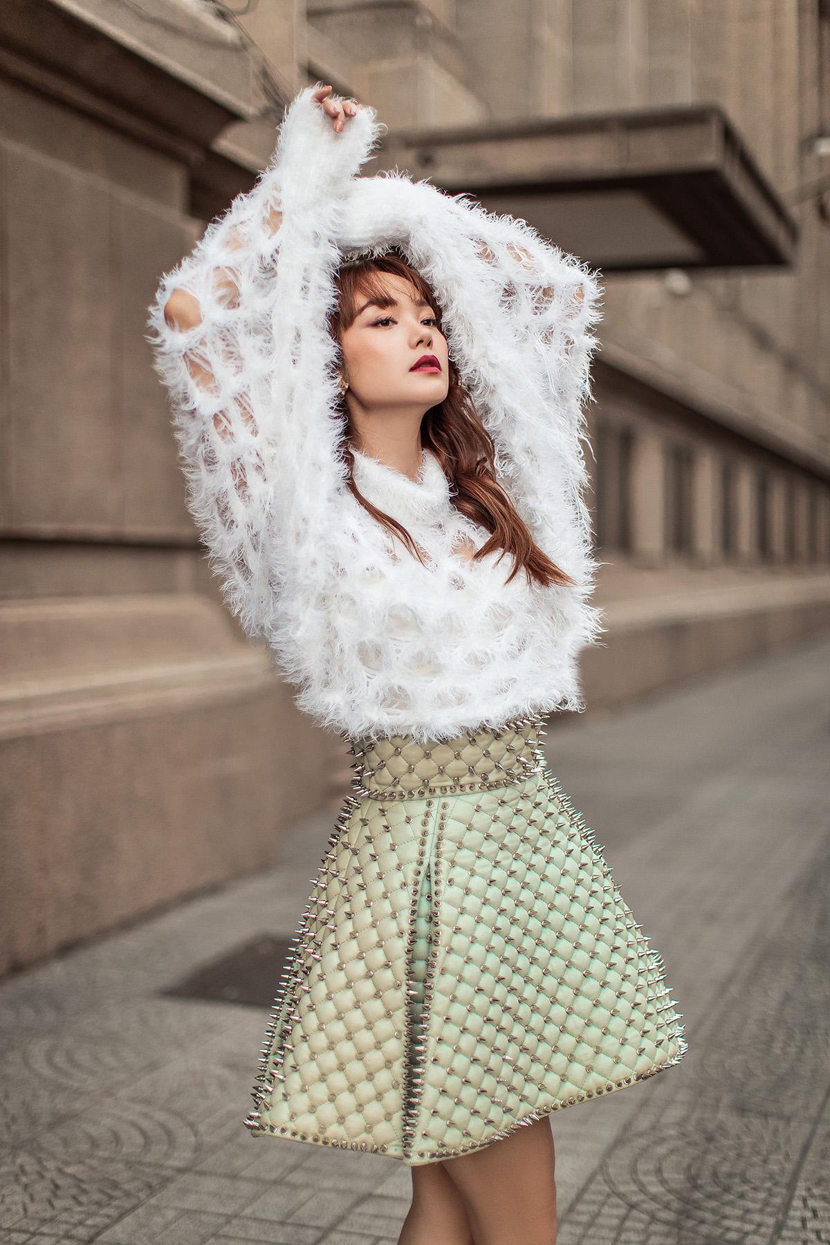 Chân váy màu xanh pastel được Minh Hằng kết hợp hài hoà với chiếc áo màu trắng trẻ trung. Nếu như chi tiết đính đinh tán mang đến sự cá tính, mạnh mẽ thì phần lông đính kết lại thể hiện sự mềm mại, quyến rũ.