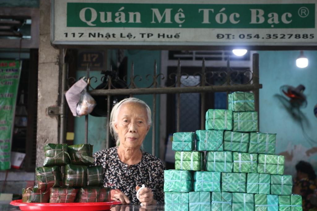 """Ở phố bánh chưng Nhật Lệ tên thật là Đào Thị Bê, ở 117 đường Nhật Lệ, địa chỉ làm bánh chưng nức tiếng gần xa. Căn nhà tuy khiêm tốn nhưng luôn rộn rã tiếng cười nói của khách ra vào. Bà Bê vào chuyện: """"Nghề này tôi tự mày mò đã lâu. Sau ngày giải phóng, mới định hình, rồi theo luôn từ đó"""". Năm nay đã 80 tuổi, bà Bê hiện chỉ bảo ban cho con cháu trong nhà làm nghề."""