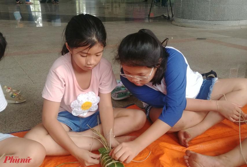 Mấy đứa trẻ theo bà, theo mẹ tham gia hội thi và tập tành gói bánh Tét.