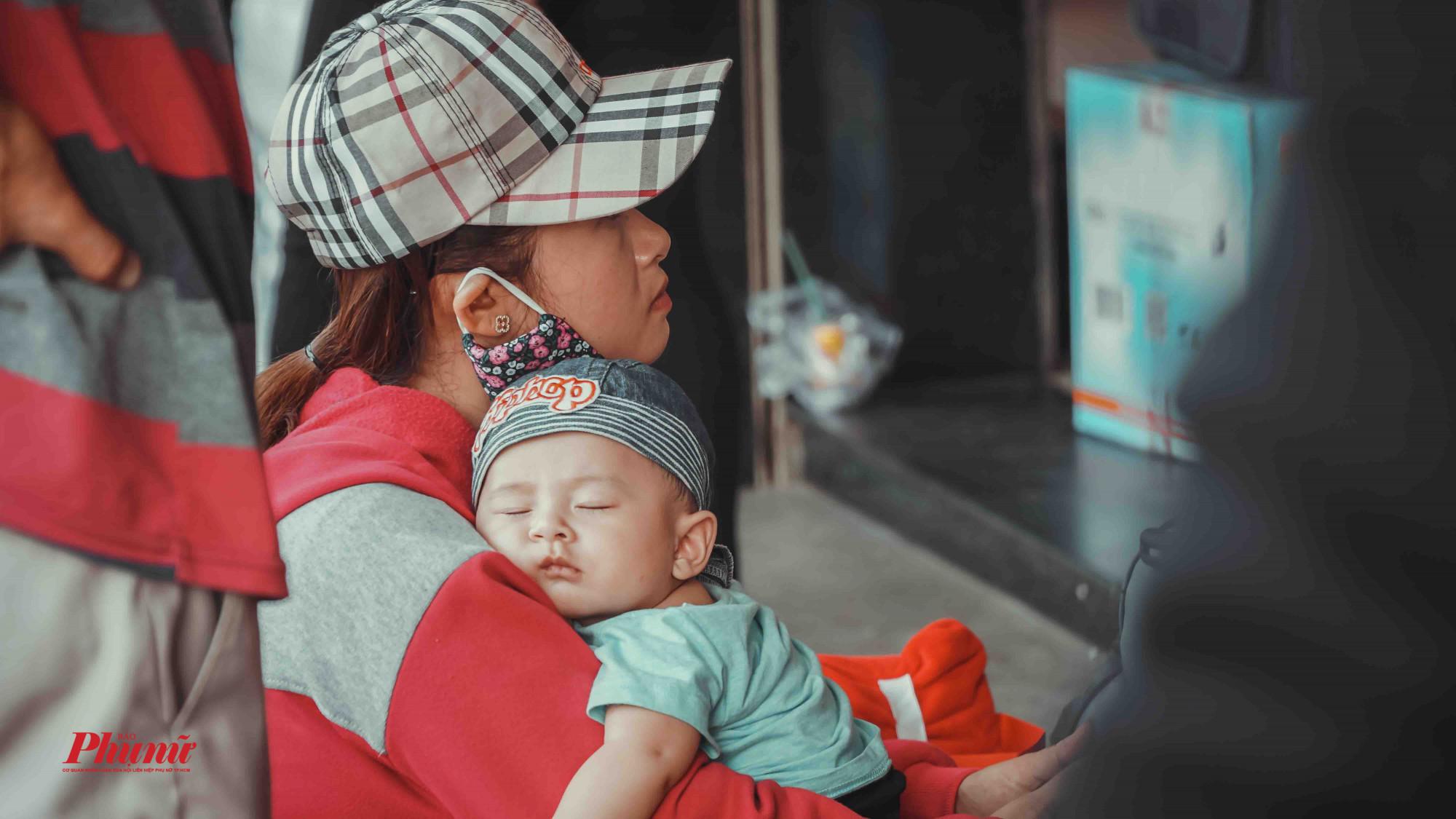 Một bé trai mệt nhừ ngủ trên vai mẹ