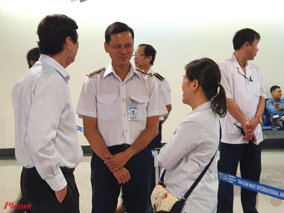 Nhân viên an ninh tại sân bay Tân Sơn Nhất TPHCM trao đổi với bác sĩ Hưng về công tác phòng, chống dịch.