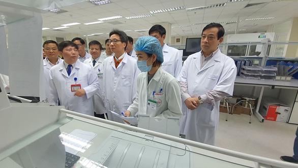 Phó Thủ tướng Vũ Đức Đam (thứ 3 từ phải) kiểm tra phương tiện xét nghiệm tại Bệnh viện Bệnh nhiệt đới Trung ương - Ảnh: BYT