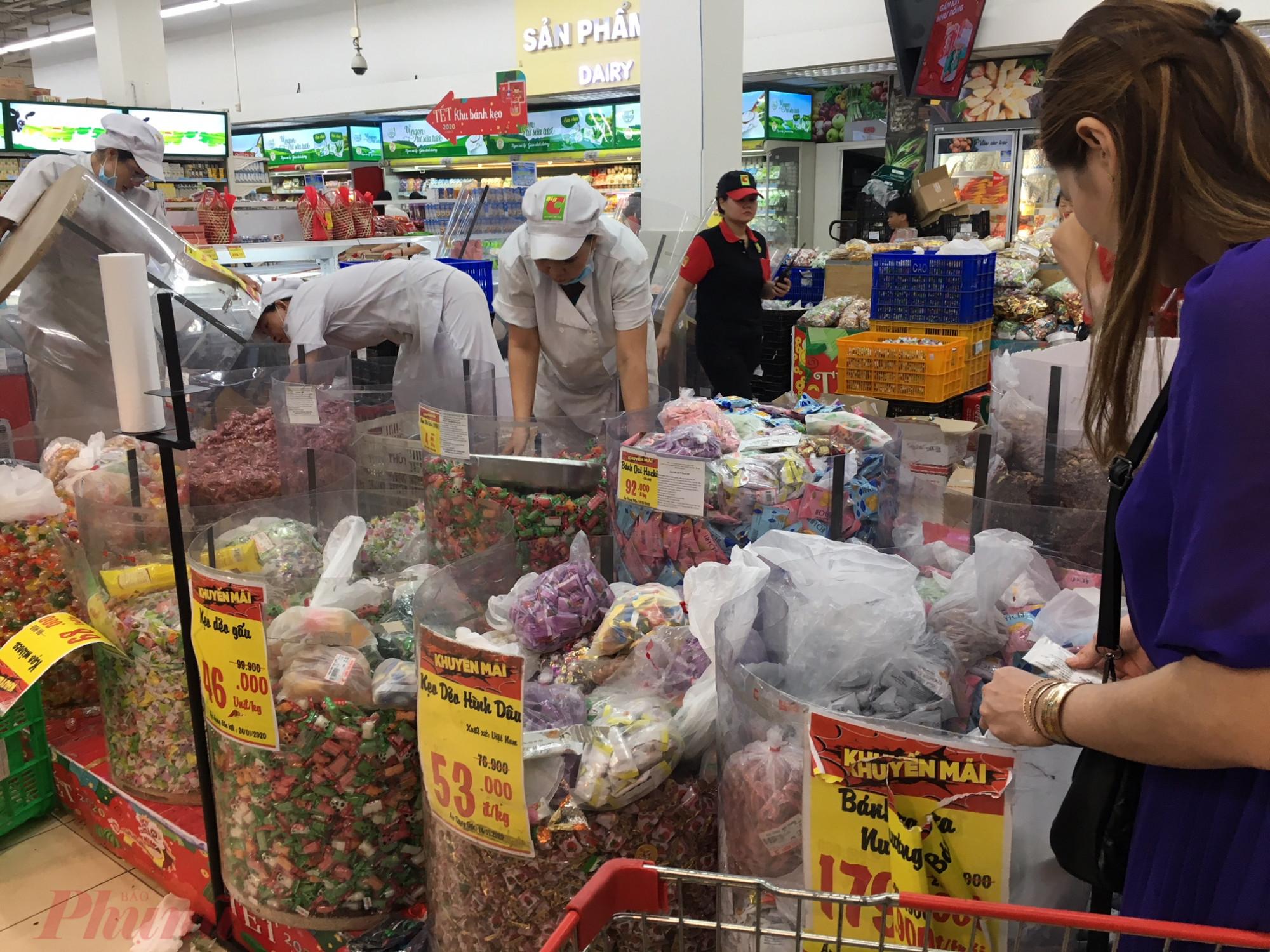 Người tiêu dùng chen chúc nhau mua bánh mứt kẹo cân kýtại siêu thị Big C Gò Vấp sau khi các mặt hàng này tiếp tục giảm giá. Nhân viên siêu thị phải liên tục châm hàng.