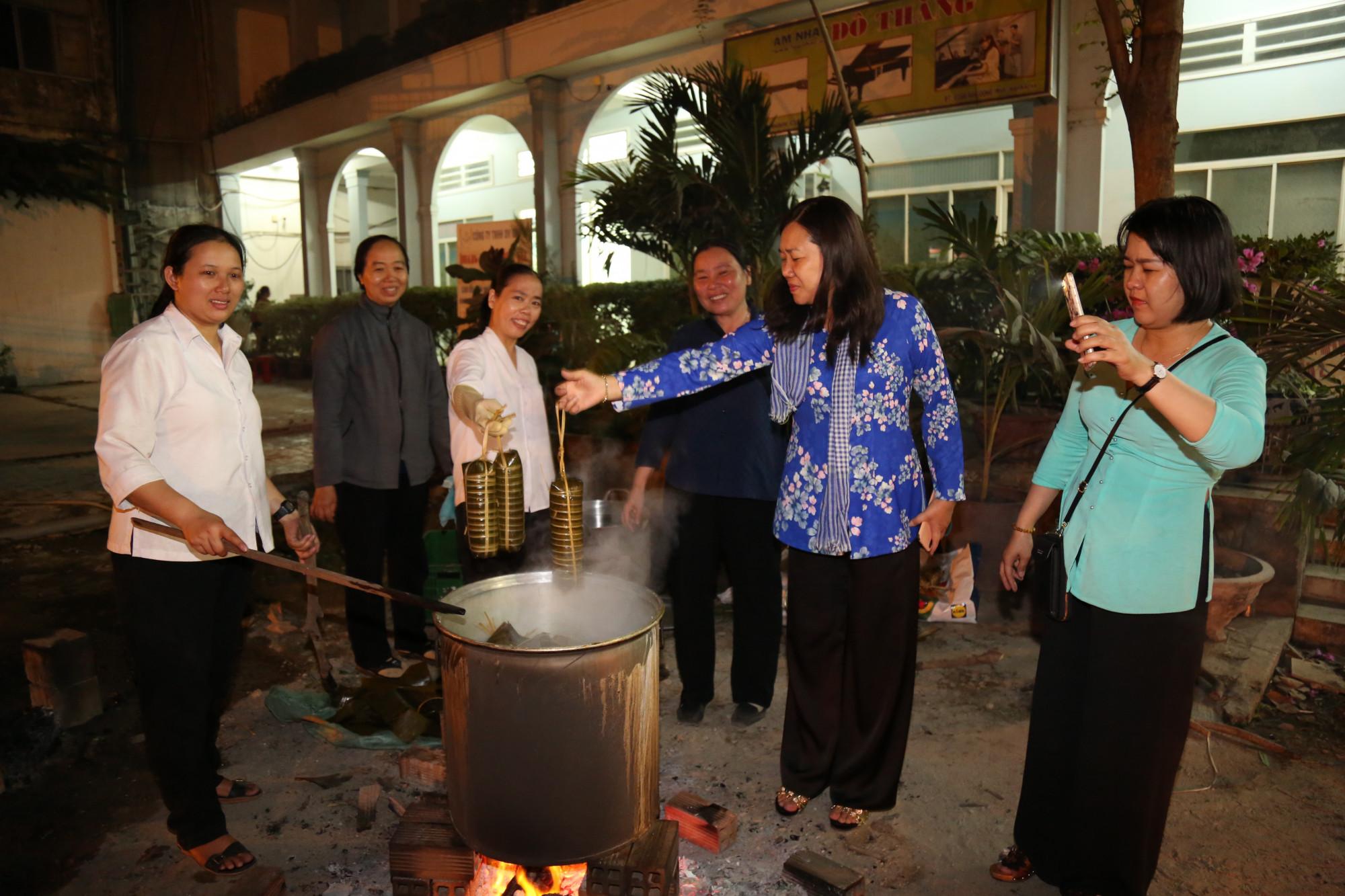 Bà Nguyễn Thị Tuyết Nga (thứ 2, từ phải qua) - Chủ tịch Hội LHPN quận 2 - cùng các sơ canh lửa, vớt bánh tét.