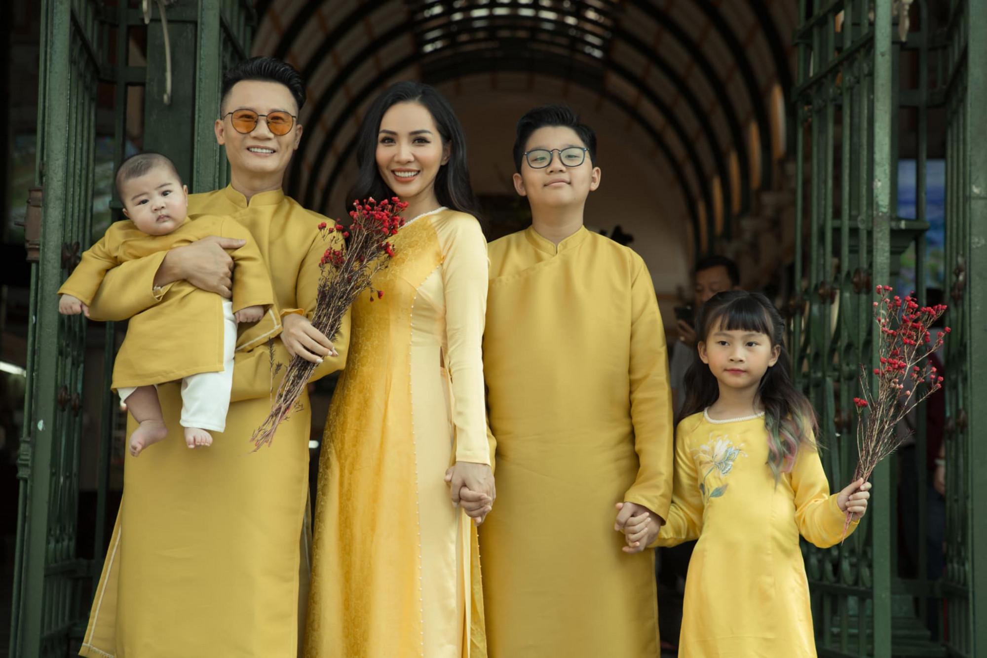 Gia đình ca sĩ Hoàng Bách diện áo dài tông xuyệt tông vàng bắt mắt.