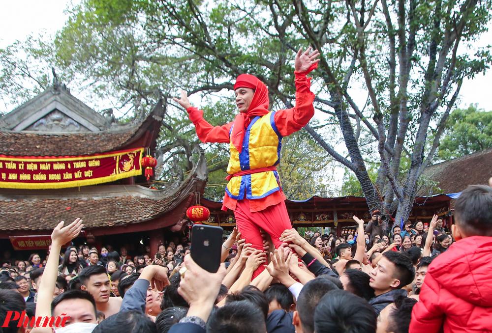 Vị quan đám được các thanh niên đỡ đi ra sân đình để biểu diễn cho người dân xem.