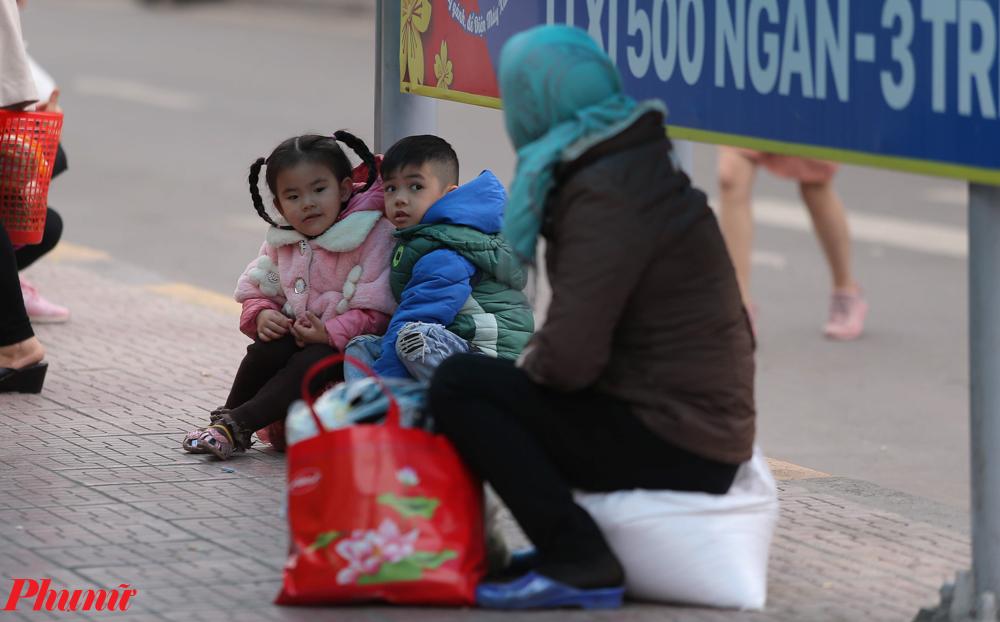 Những đứa trẻ ngồi chờ cha mẹ đi lấy đồ.