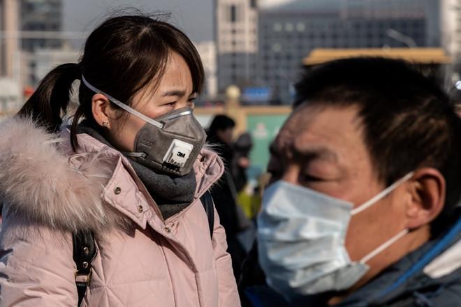 Người dân đeo khẩu trang gần một trạm xe điện tại Bắc Kinh AFP