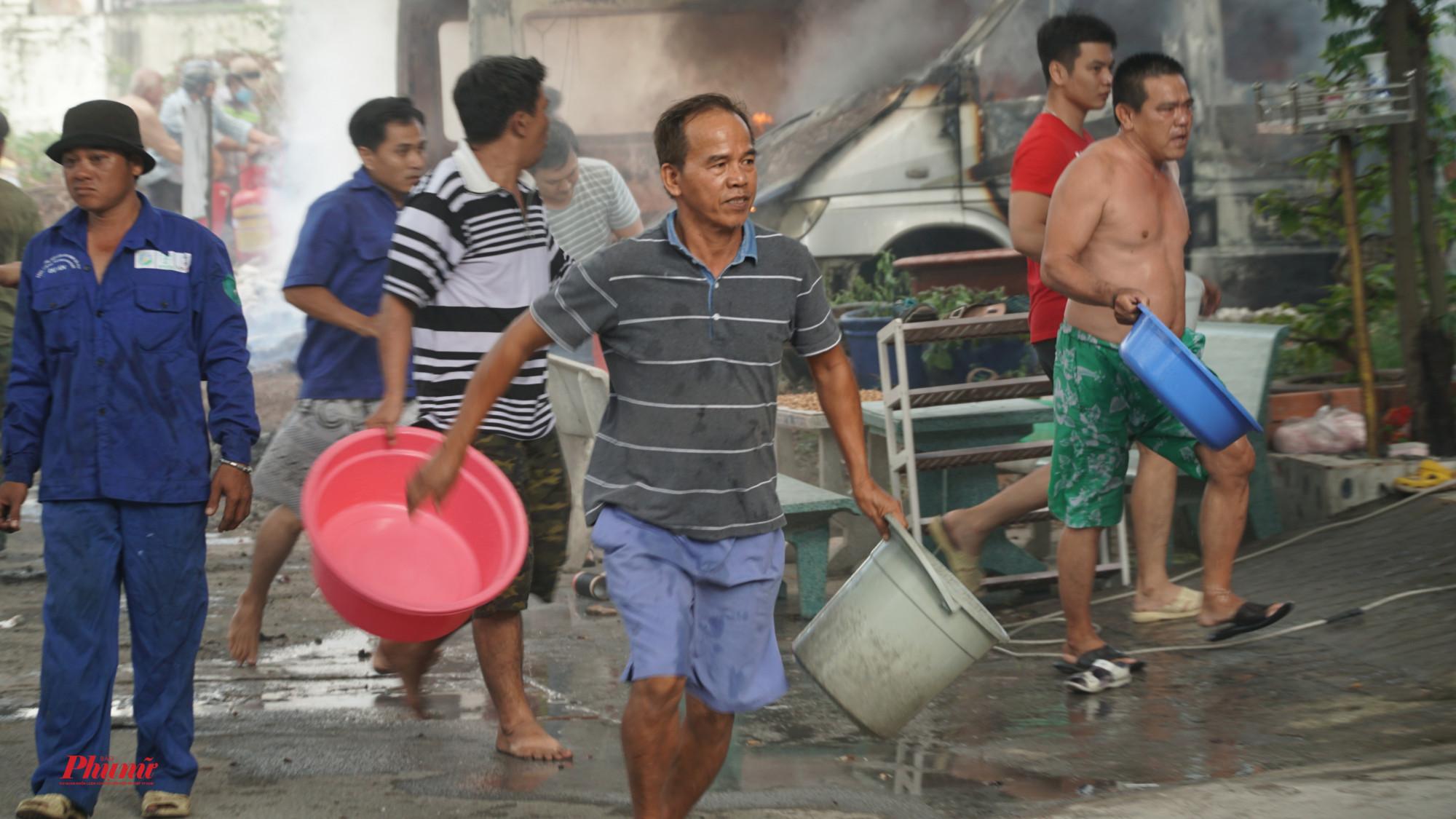 Mọi người đem thau, chậu hứng nước dập lửa