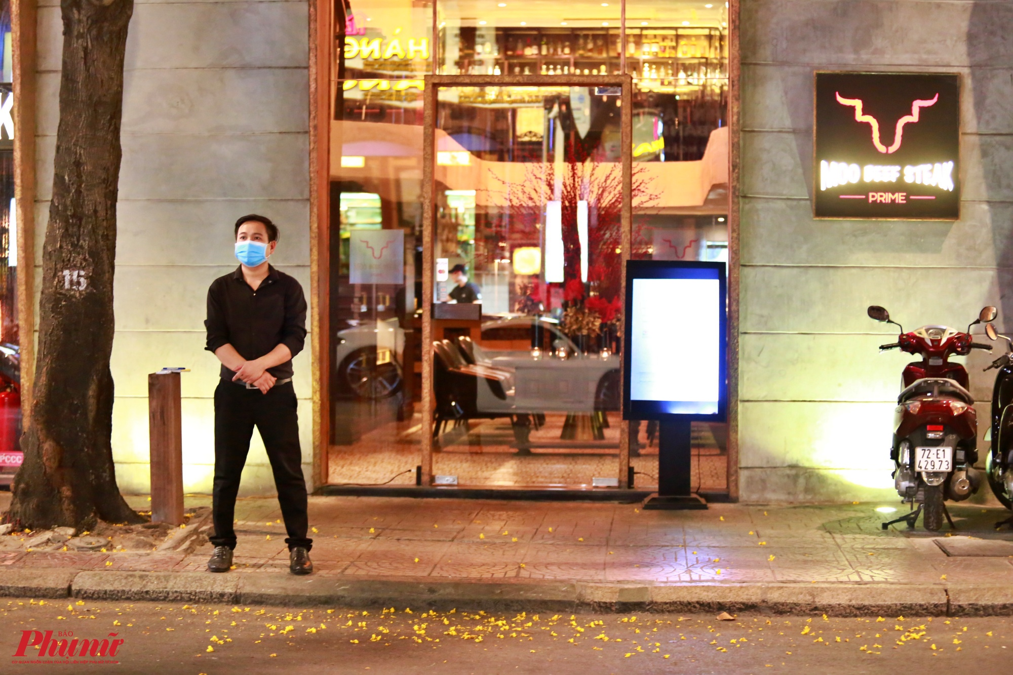 Một nhân viên nhà hàng bịt khẩu trang đợi khách ở đường Ngô Đức Kế