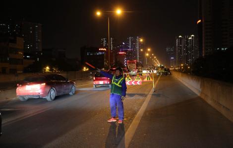 Nhiều công nhân làm việc xuyên đêm bên làn xe lao vun vút để sửa chữa đường trên cao