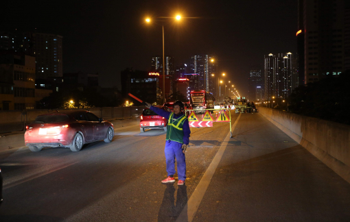 Nhiều công nhân xuyên đêm sửa đường trên cao, bên làn xe lao vun vút
